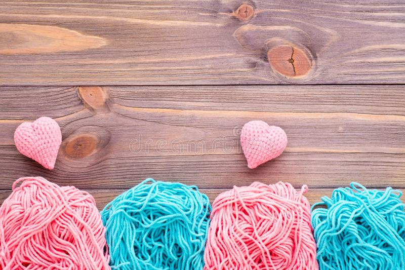 Tangles of pink and mint yarn and knitting hearts stock photo