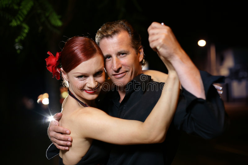 Tango. Happy young adult couple dancing outdoors at night, close-up royalty free stock images