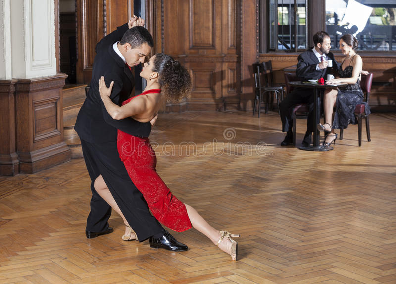 Tango Dancers Performing While Mid Adult Couple Dating. Confident tango dancers performing while mid adult couple dating in restaurant stock photos