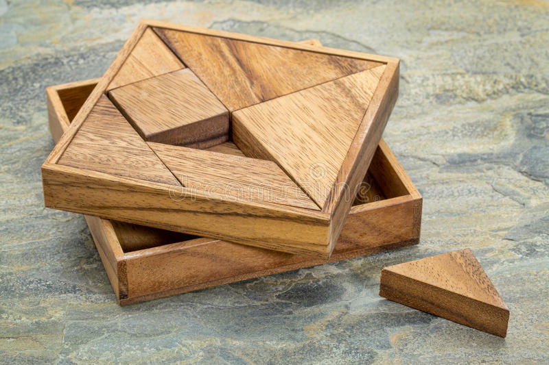 Tangram - Chinese puzzle game. Tangram, a traditional Chinese Puzzle Game made of different wood parts to build abstract figures from them, slate rock background royalty free stock photo
