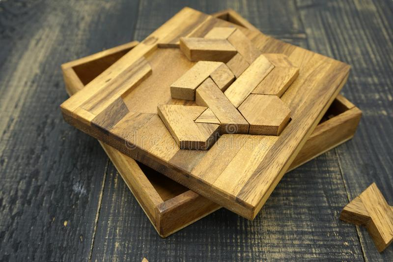 Tangram, Chinese traditional puzzle game. Made of different wood parts that come together in a distinct shape, in a wooden box stock images