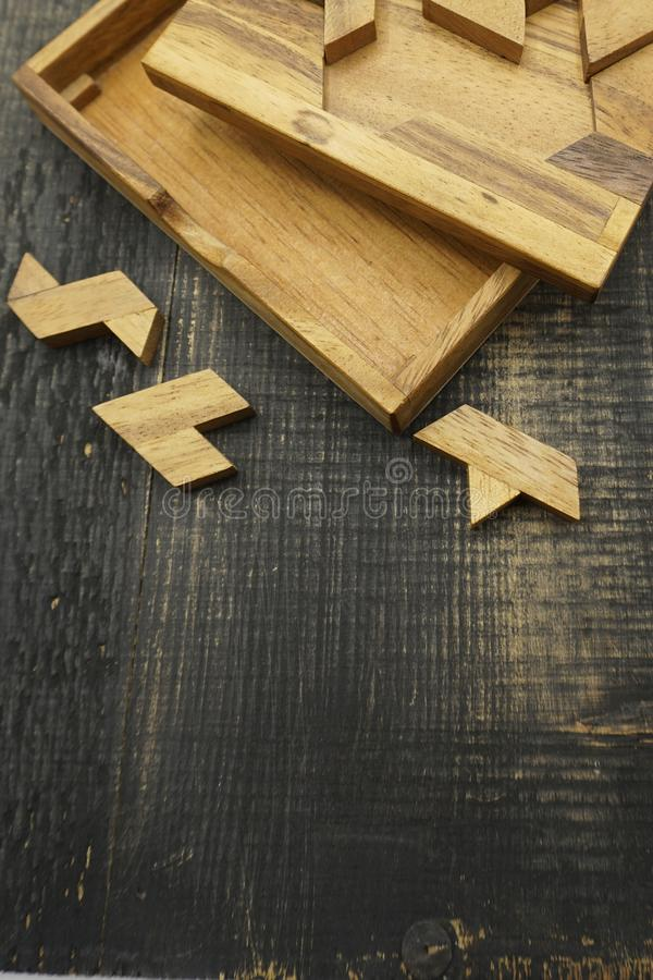 Tangram, Chinese traditional puzzle game. Made of different wood parts that come together in a distinct shape, in a wooden box royalty free stock images