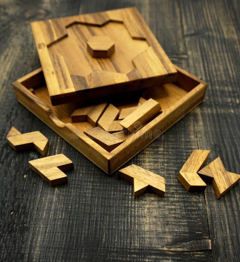 Tangram, Chinese traditional puzzle game. Made of different wood parts that come together in a distinct shape, in a wooden box royalty free stock image