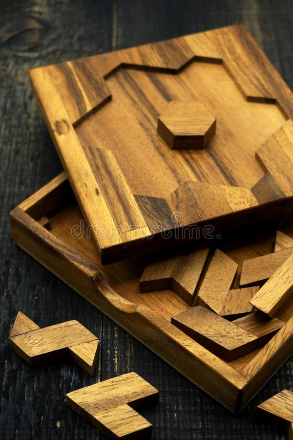 Tangram, Chinese traditional puzzle game. Made of different wood parts that come together in a distinct shape, in a wooden box royalty free stock photo