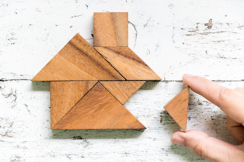 Tangram wait to fulfill home shape on old white wood background conept for build dream home, happy life, house or mortgage. Tangram puzzle wait to fulfill home stock photo
