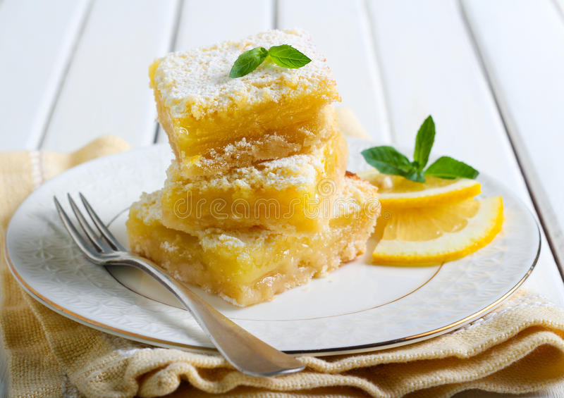 Tangy lemon squares. With icing sugar on plate royalty free stock image