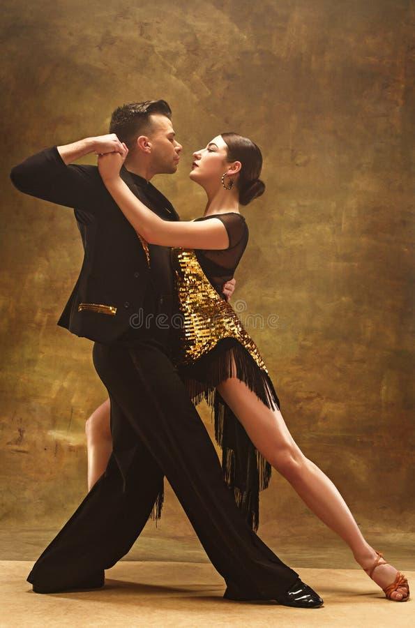 Taniec sala balowej para w złoto sukni tanu na pracownianym tle obraz stock