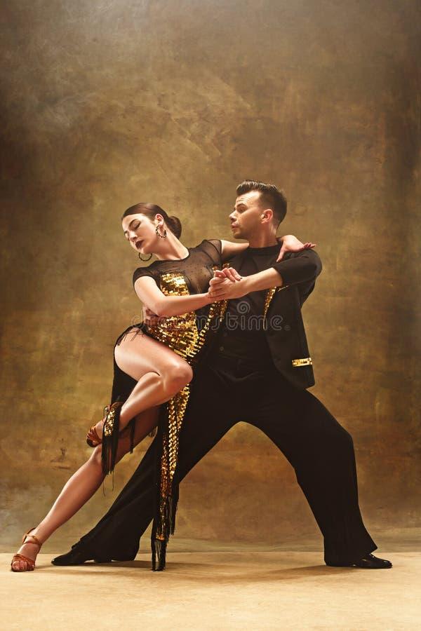 Taniec sala balowej para w złoto sukni tanu na pracownianym tle obraz royalty free