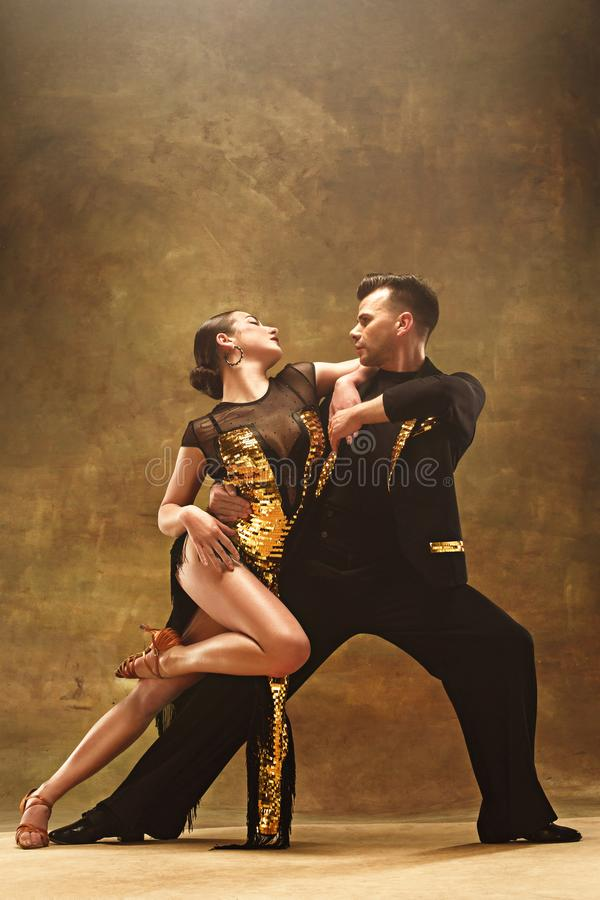 Taniec sala balowej para w złoto sukni tanu na pracownianym tle fotografia royalty free