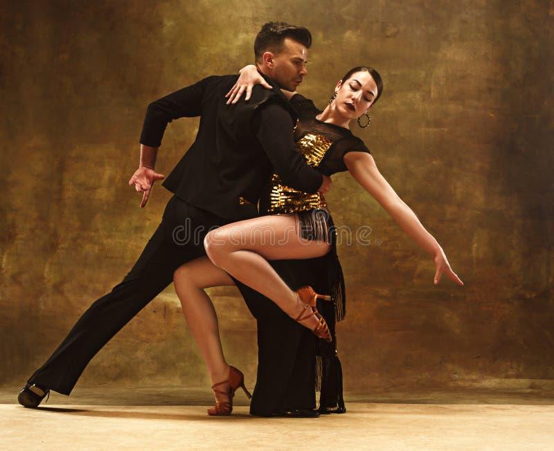 Taniec sala balowej para w złoto sukni tanu na pracownianym tle obrazy stock