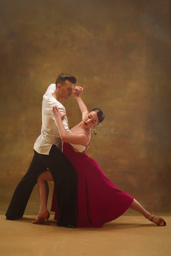 Taniec sala balowej para w złoto sukni tanu na pracownianym tle obrazy royalty free
