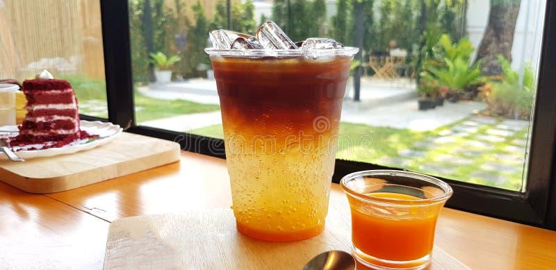 Tanjerina do ginger ale do café do gelo com fundo vermelho do bolo, da janela e da planta verde fotos de stock royalty free