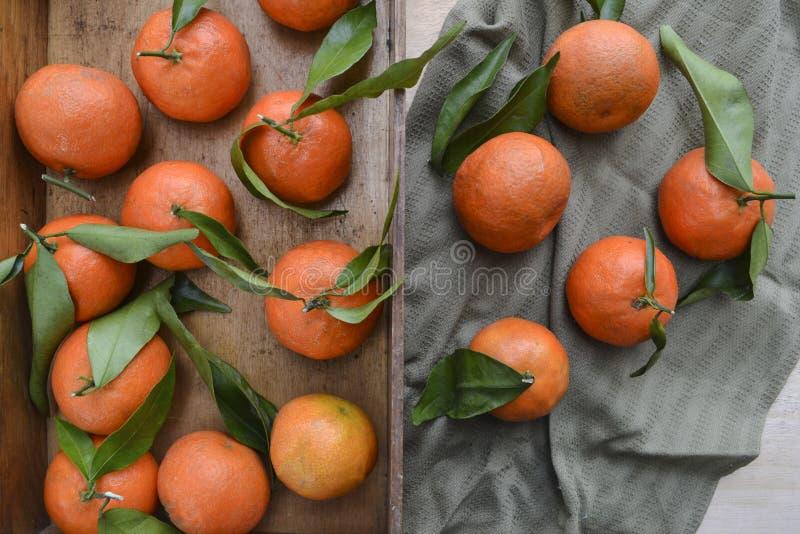 Tanjerinas frescas fruto ou tangerinas com as folhas na caixa de madeira na tabela imagem de stock