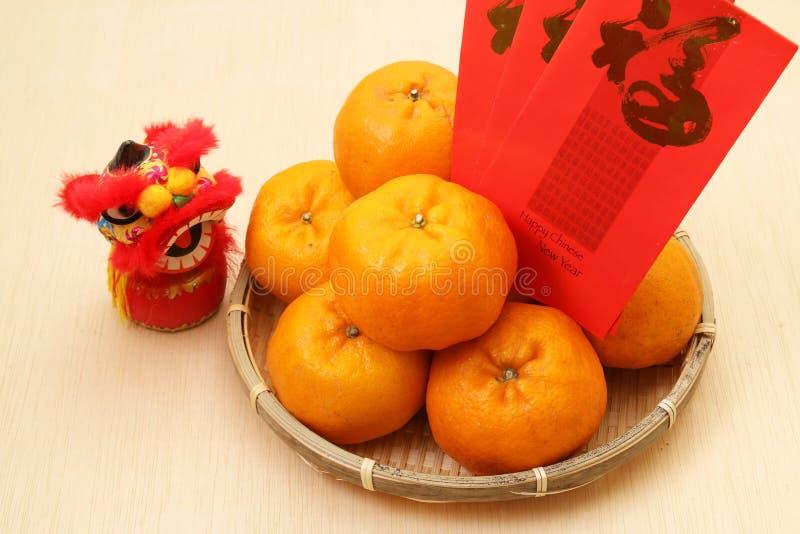 Tanjerinas na cesta com os pacotes vermelhos chineses do ano novo e a boneca do leão fotografia de stock