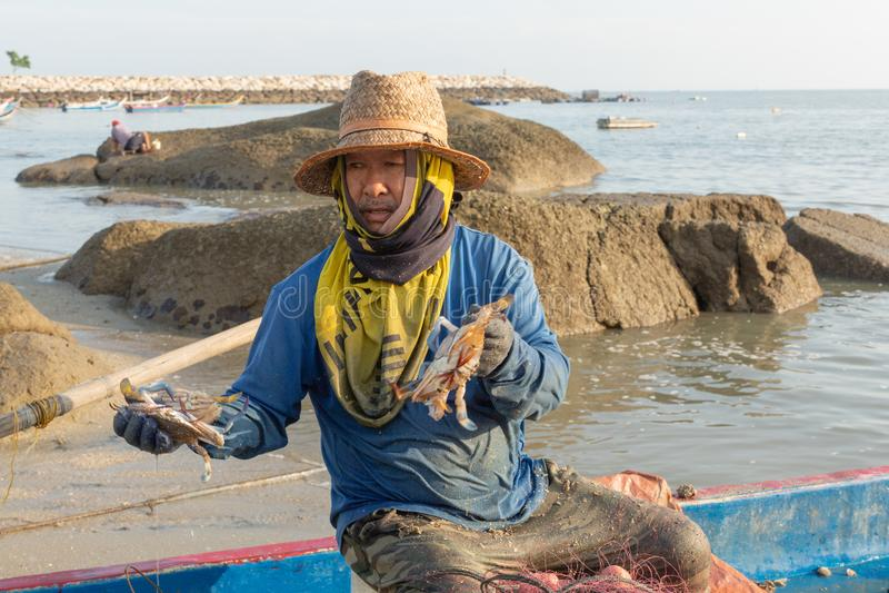 Local fisherman in his fishing boat,sorting his morning catch of crab. Tanjung Tokong Beach, Penang Island, Malaysia: December 25, 2018: Local fisherman in his stock images