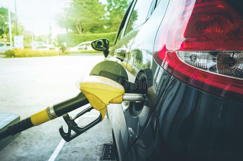 Tank de pomp in auto bij benzinestation bij stock fotografie
