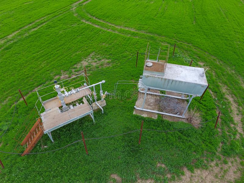 Equipment of an oil well. A tank with methanol near the oil well. Shutoff valves and service equipment. A tank with methanol near the oil well. Equipment of an stock image