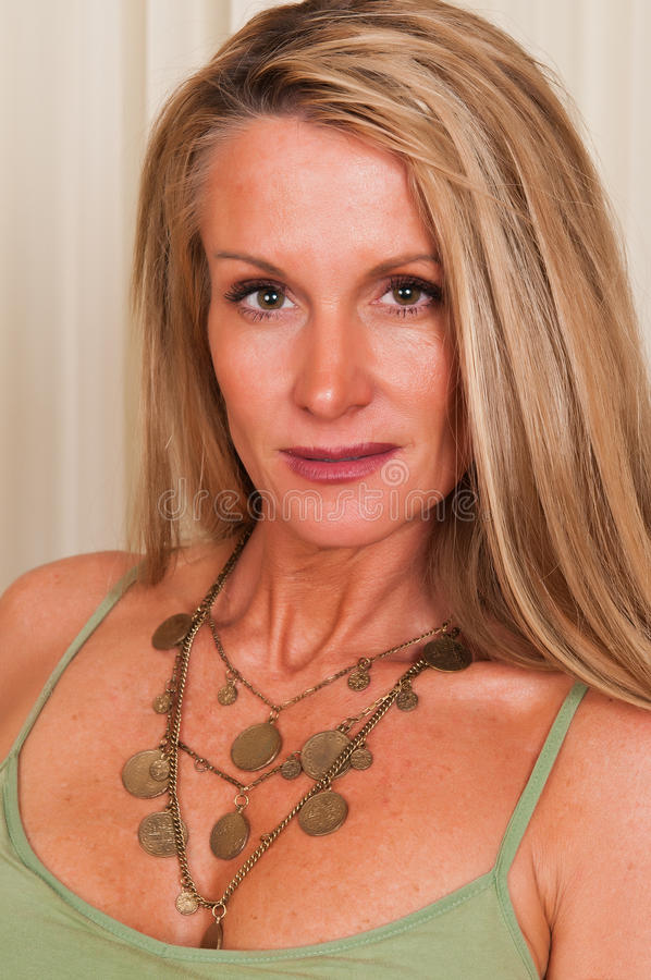 Tank top. Beautiful mature blonde in a green tank top stock image