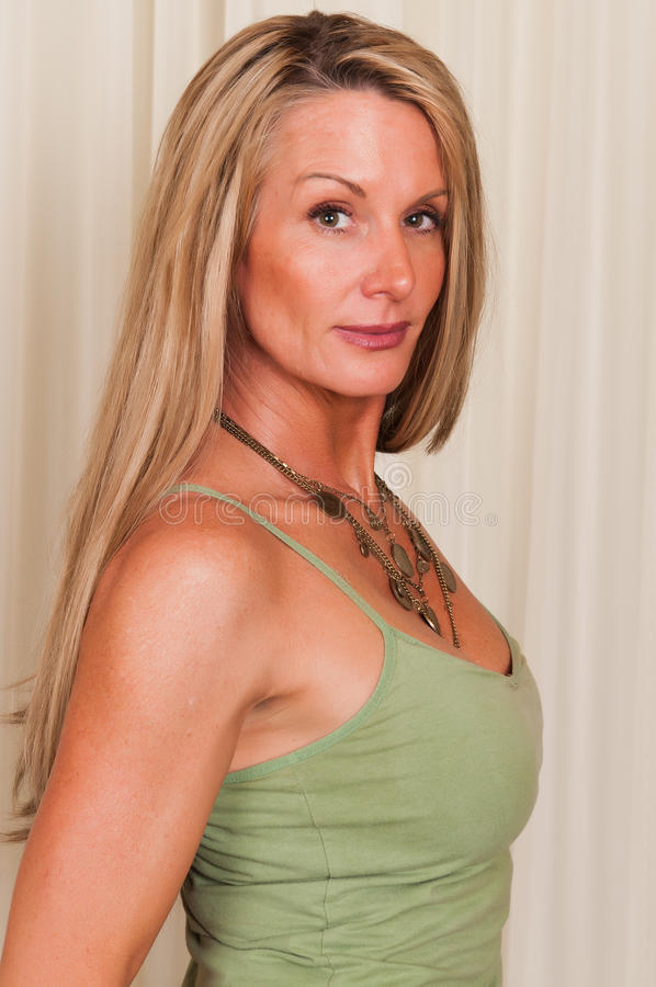 Tank top. Beautiful mature blonde in a green tank top royalty free stock photography