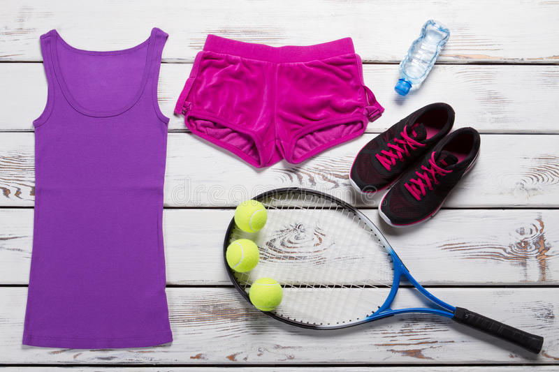 Tank top with sport shorts. Female tennis outfit on table. Tennis equipment with water bottle. Move quickly and win royalty free stock photography