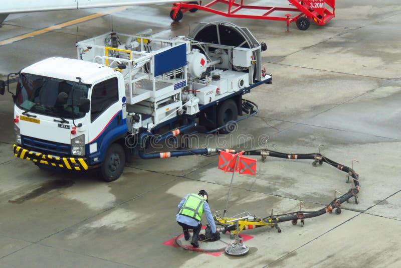 Tank vrachtwagen voor geparkeerd vliegtuig bij en wachtend tank het vliegtuig op grond in de luchthaven bij royalty-vrije stock fotografie