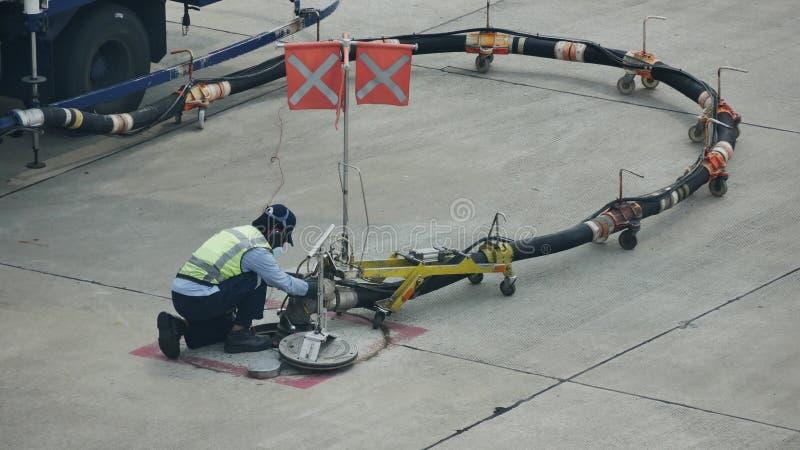 Tank vrachtwagen voor geparkeerd vliegtuig bij en wachtend tank het vliegtuig op grond in de luchthaven bij stock afbeeldingen