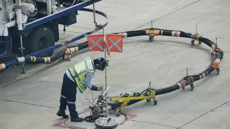 Tank vrachtwagen voor geparkeerd vliegtuig bij en wachtend tank het vliegtuig op grond in de luchthaven bij stock afbeelding