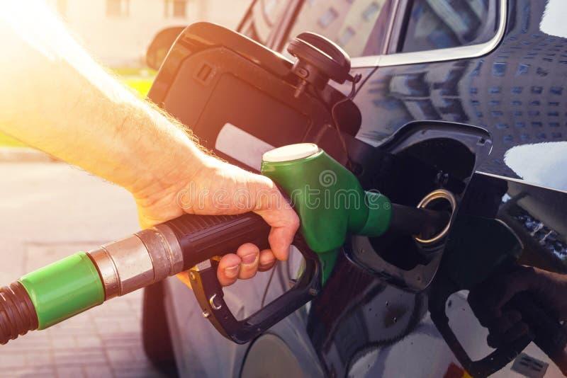 Tanka bilen på en bensinstationbränslepump Manchaufförhanden som fyller på och pumpar bensinolja bilen med bränsle på tankar han, royaltyfri fotografi