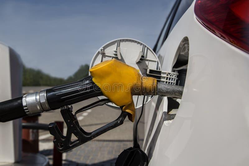 Tanka på bensinstationen Gammal gul pistol med en slang i gasbehållaren av bilen arkivfoto