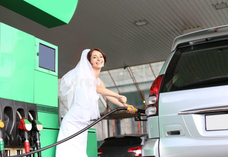 Tankar den vita klänningen för bruden bilbensinstationen royaltyfri bild