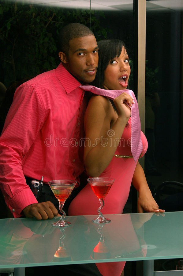 Tanked and Tagged. African American couple in a martini bar.Man being lead off playful by woman pulling his necktie
