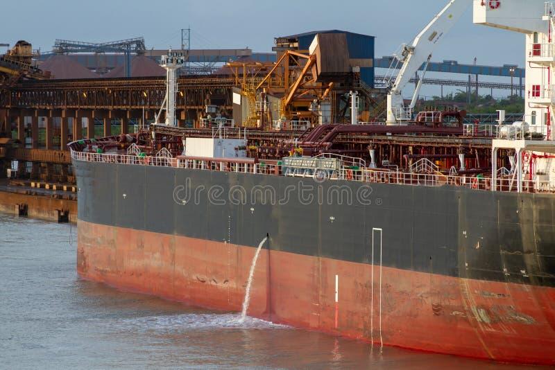 Tanker die koelwaterwater in havenwateren lossen in avondtijd stock foto