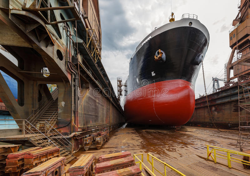 Tanker in dry dock. A large tanker ship is being renovated in shipyard Gdansk, Poland royalty free stock images
