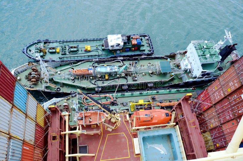 Tanker längsseits des großen Containerschiffs stockbilder