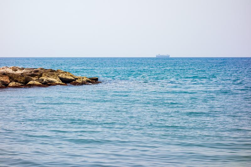Oil tank ship on the sea. A tanker sails along the horizon line of an ocean and some rocks off the coast royalty free stock photography