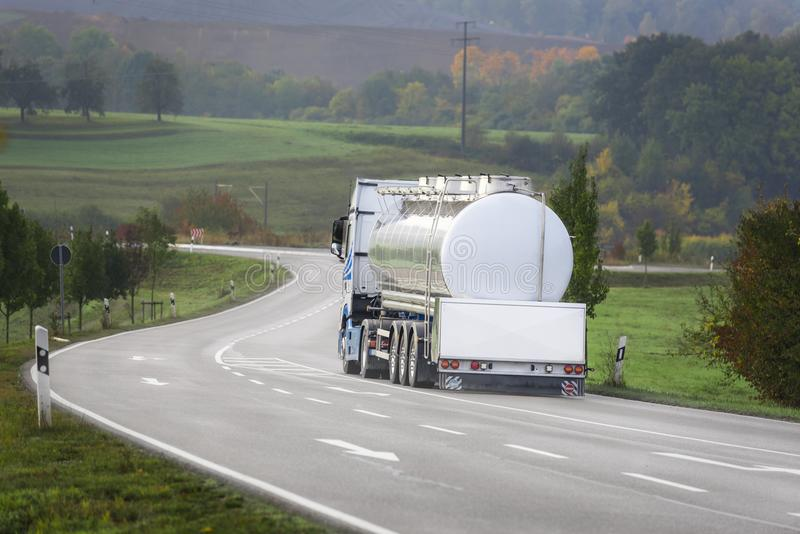 Tanker truck on the road. Big white tanker truck drives on a countryside road, outside the german city Schwabisch Hall, Baden Wurttemberg, Germany stock image