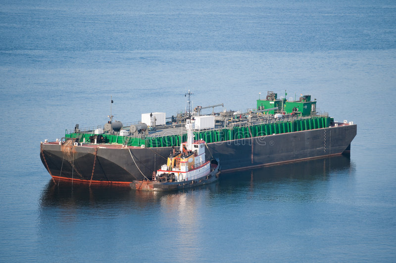 Tanker and a tugboat. Tugboat pushing a tanker barge stock photography