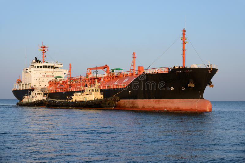 Tanker and tugboat. In a port royalty free stock images