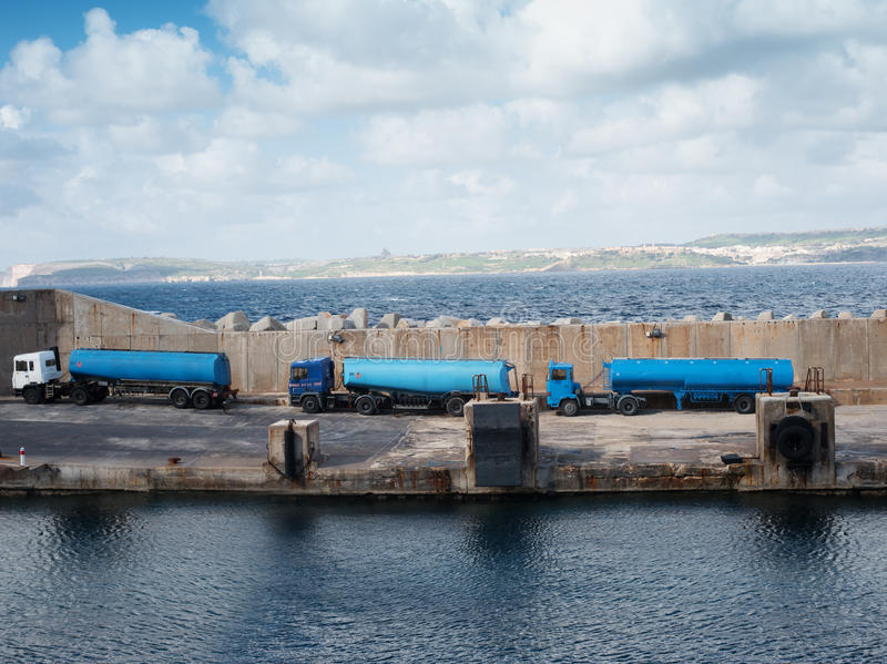 Tankers lined up on a cement wharf royalty free stock photography