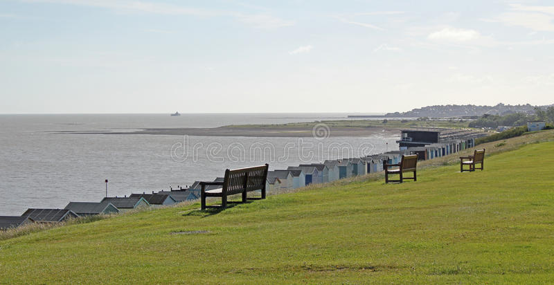 Tankerton Slopes And Yacht Club. This photo shows some benches and beach huts on Tankerton Slopes with the yacht club to the right and beyond royalty free stock photos
