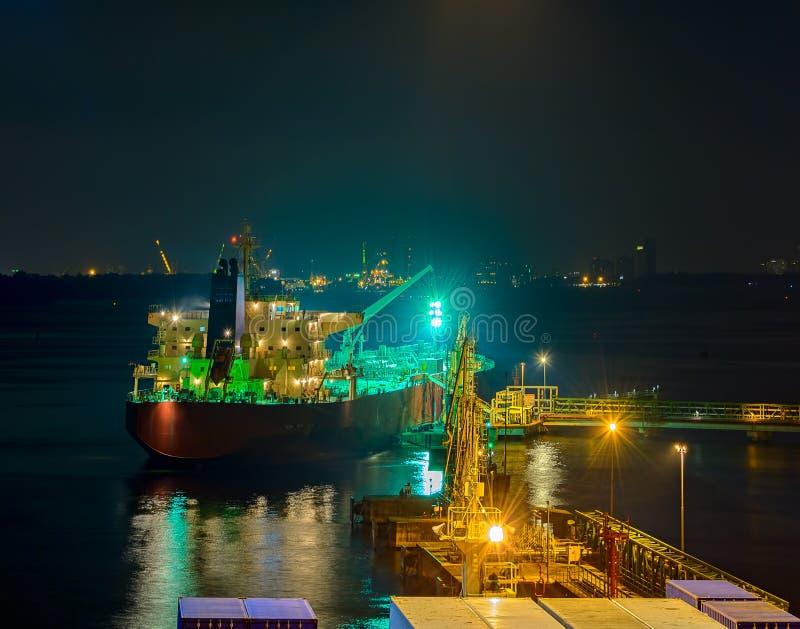 Tankfartyg för olje- produkter under lastoperationer på natten royaltyfria bilder