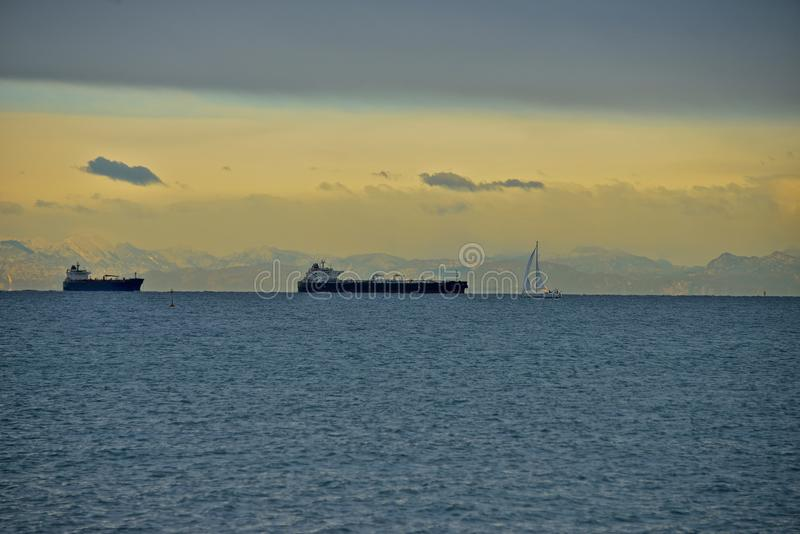 Tankfartyg för två skepp och en segelbåt i mitt av havet royaltyfri bild