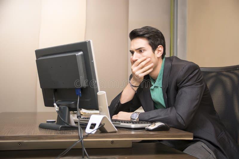 Tankfull bekymrad ung man som stirrar på datoren royaltyfri foto