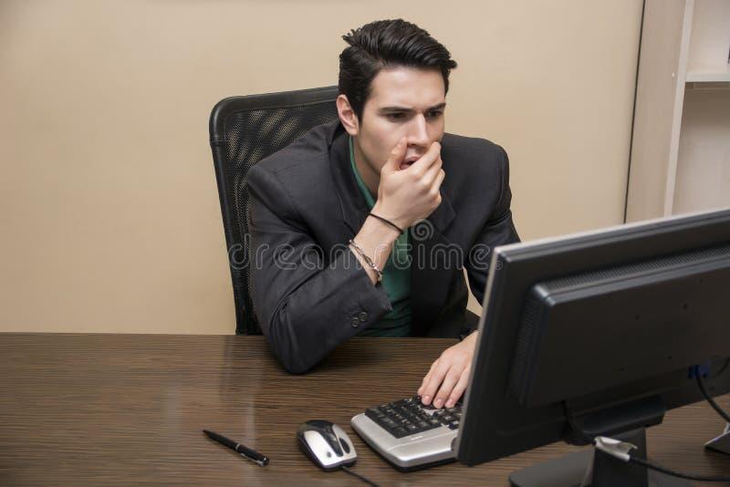Tankfull bekymrad ung man som stirrar på datoren fotografering för bildbyråer