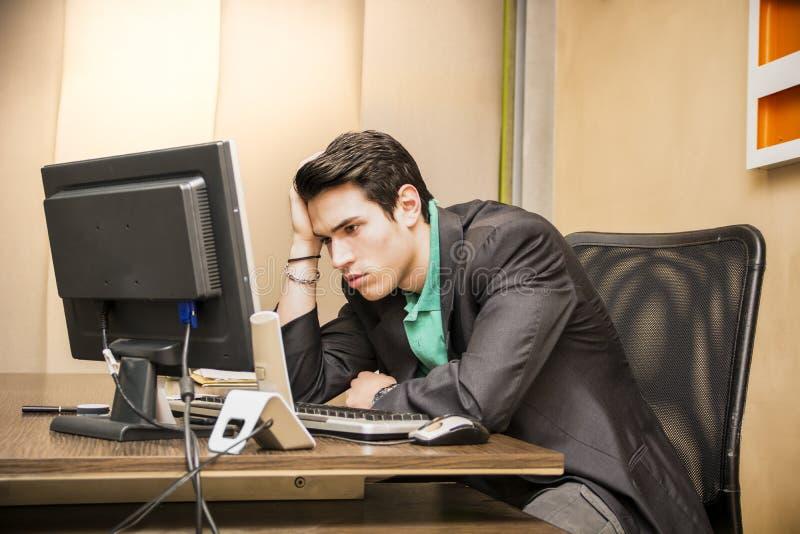 Tankfull bekymrad ung manlig arbetare som stirrar på datoren royaltyfria bilder