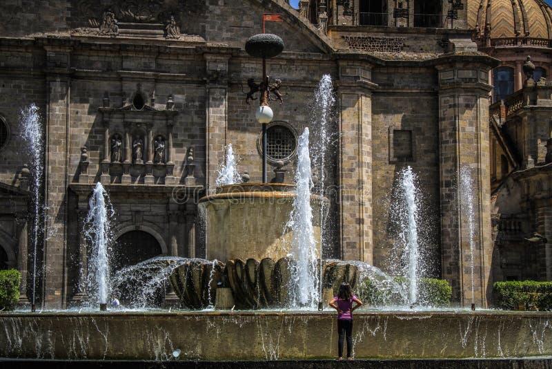 Tankfull liten flicka framme av springbrunnen av den Guadalajara domkyrkan, Jalisco, Mexico royaltyfri foto