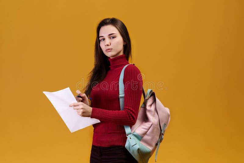 Tankfull stående av den gulliga flickan på isolerad bakgrund i röd tröja fundersam ung kvinna med förbryllat uttryck arkivfoto