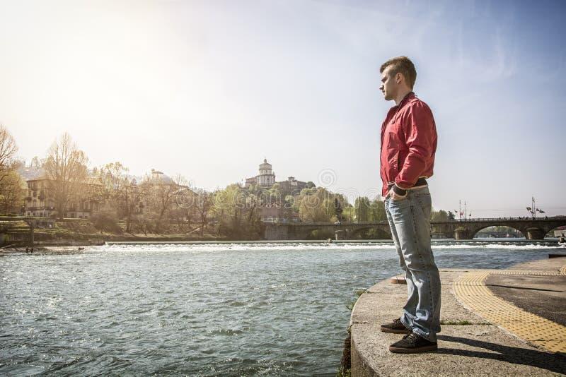 Tankfull ung man som sitter bredvid floden i Turin arkivfoton