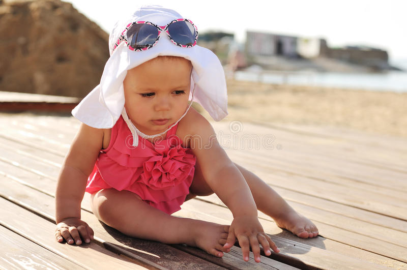 Tanned baby on the beach. Tanned baby girl on the beach royalty free stock photo