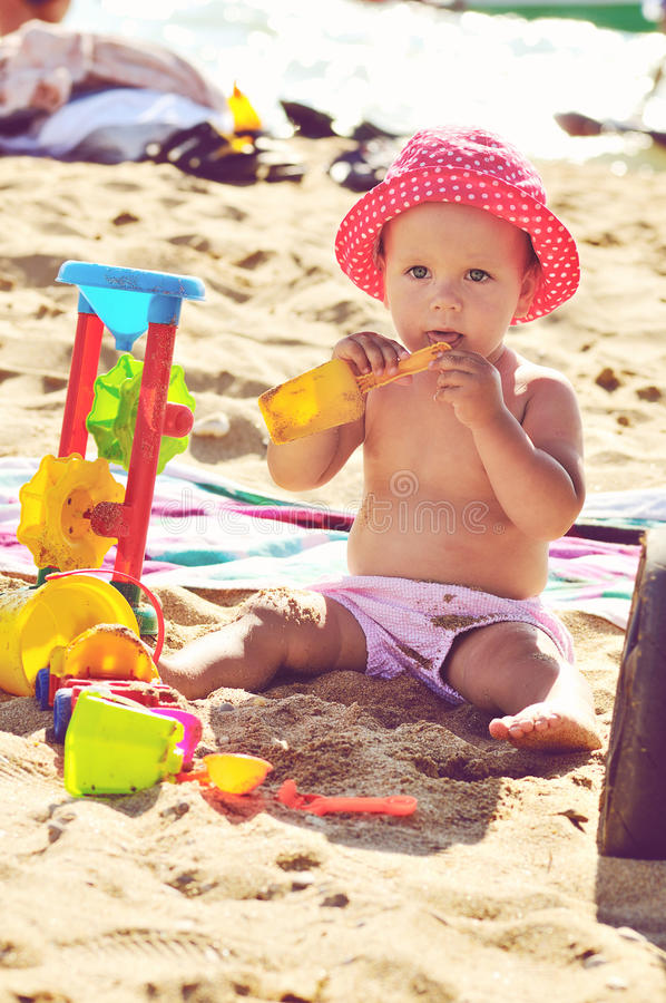 Tanned baby. Playing on the beach in backlit stock photos